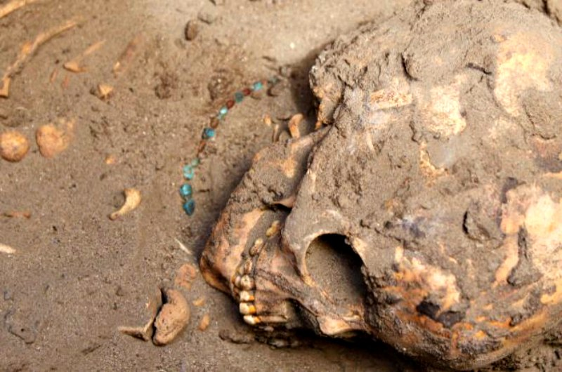 Restos óseos de un niño con un collar hallados en uno de los enterramientos de Tombos. (Fotografía: El Mundo/Purdue University)