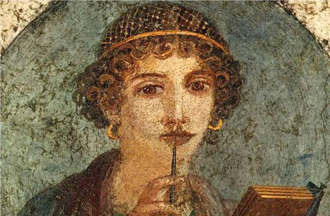 """Detalle de un fresco romano del siglo I d. C. en el que se observa a una joven con un lápiz (stylus) de los que se utilizaban para escribir en tablillas de cera. La redecilla de su pelo estaba confeccionada con hilo de oro, de moda en la época de Nerón. Ésta es una de las pinturas romanas más famosas y admiradas, popularmente conocida como """"Safo"""" , aunque en realidad se trata de una joven de la alta sociedad pompeyana que luce grandes pendientes de oro. Dominio Público"""
