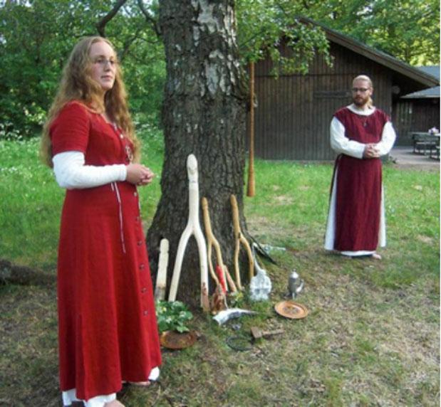 En Suecia, una sacerdotisa y un sacerdote paganos realizan una ceremonia durante una reunión anual. Bajo el árbol aparecen imágenes de los dioses nórdicos Thor, Frigg, Freya, Frey y Forseti, junto a un martillo ceremonial, un cuerno para beber y un anillo de juramento. Colgada del abedul, árbol sagrado para la diosa Frigg, hay una trompeta realizada, precisamente, de madera de abedul. (Public Domain)
