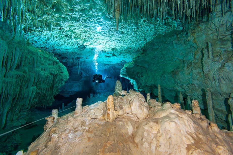 Submarinista buceando en uno de los espectaculares pasadizos decorados del sistema de cuevas del cenote Chan Hol, México. (Alison Perkins/Underwater Project)