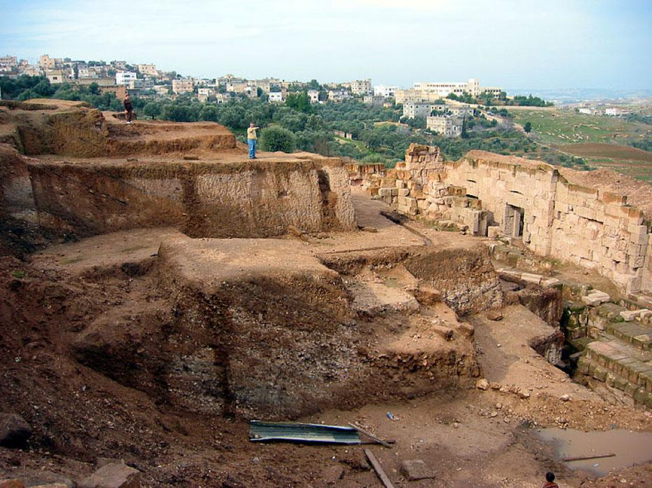 La tumba fue descubierta en Beit Ras, población ubicada en las cercanías de Irbid, Jordania. Aquí podemos ver el antiguo teatro de Capitolias en el yacimiento arqueológico situado a las afueras de la ciudad, con Beit Ras al fondo. (CC BY-SA 4.0)