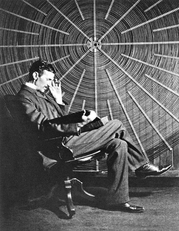 """Nikola Tesla leyendo el libro de Rudjer Boscovich """"Theoria Philosophiae Naturalis"""" en su laboratorio de Nueva York ante la enorme bobina de uno de sus transformadores de alto voltaje (Public Domain)"""