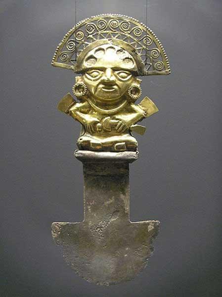 Tumi hallado en Sipán, Perú (850 d. C. – 1050 d. C.) La figura de oro que decora el mango representa a un dignatario ricamente ataviado, posiblemente un sacerdote, quien a su vez también empuña en su mano izquierda un tumi sacrificial. En los lóbulos de las orejas de esta figura había originalmente turquesas incrustadas. El reverso de este tumi está decorado con una lámina de oro en forma de lágrima. (Public Domain)