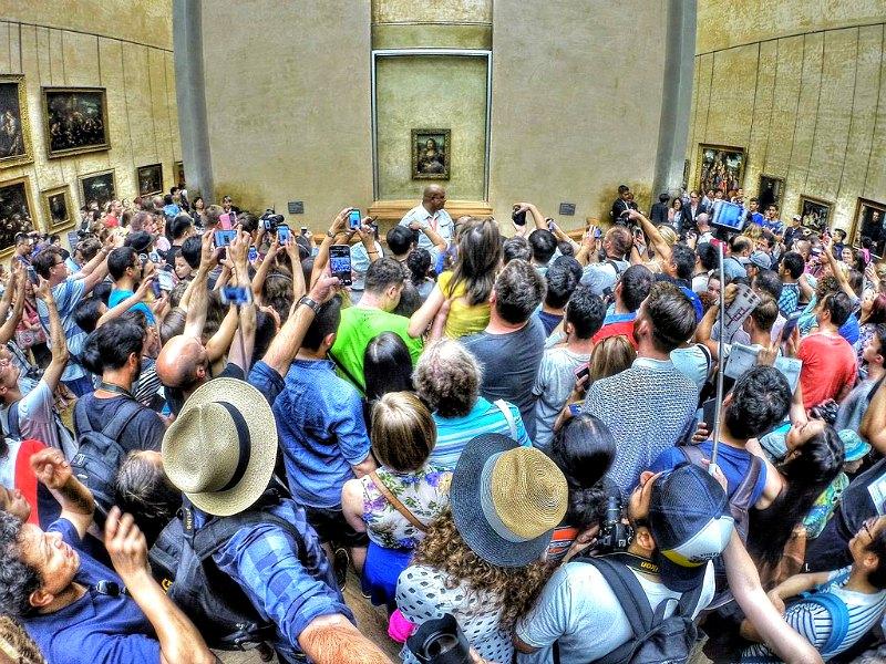 Cada año más de 8.000.000 de personas visitan el Museo del Louvre parisino. En la imagen, turistas agolpándose en torno al retrato de la Mona Lisa. (Max Fercondini/CC BY-SA 4.0)