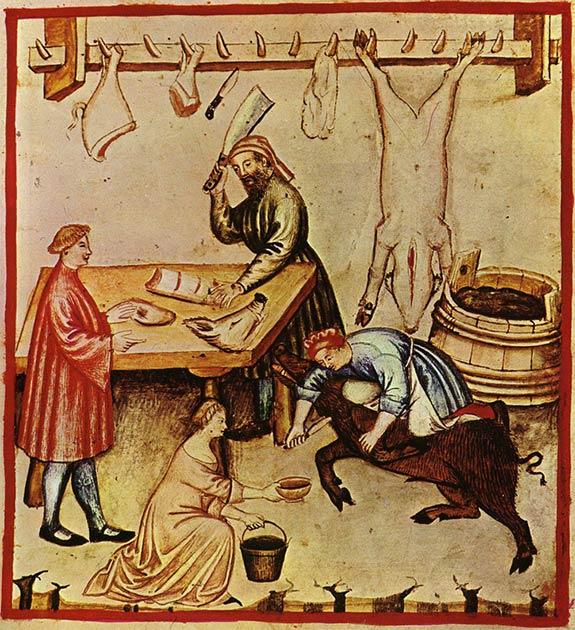 Una carnicería del siglo XIV. Se está desangrando un gran cerdo en preparación para el sacrificio. Una carcasa y cortes de cerdo están colgando de un estante y se están preparando varios cortes para un cliente. (Dominio publico)