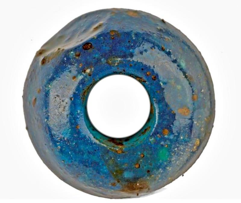 Pequeña cuenta de vidrio azul recuperada en el yacimiento arqueológico de Must Farm (Inglaterra) datado en la Edad del Bronce. (Fotografía: La Gran Época/Must Farm)