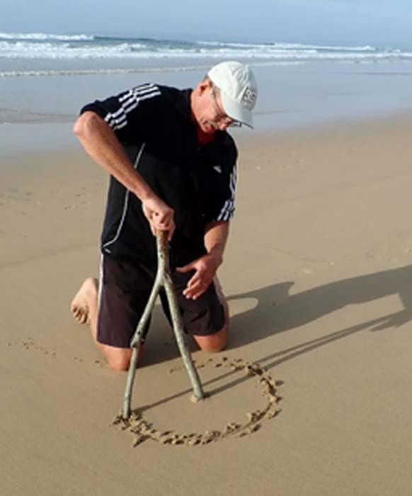 El autor demuestra cómo un humano arrodillado pudo haber usado un palo bifurcado para crear un patrón circular en la arena. (Linda Helm / The Conversation)
