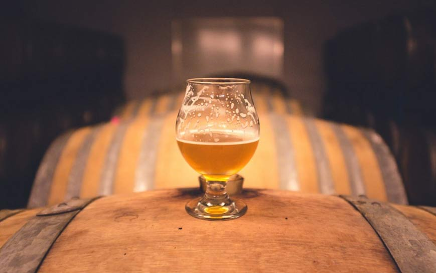 Portada-Copa de cerveza colocada sobre viejos barriles ( Public Domain )