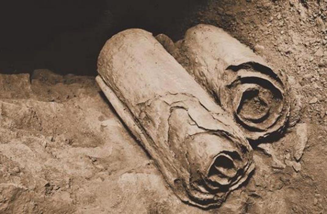 Portada - Dos manuscritos del Mar Muerto en su ubicación original de las cuevas de Qumram poco antes de ser recuperados por los arqueólogos para su conservación y estudio. (Public Domain)