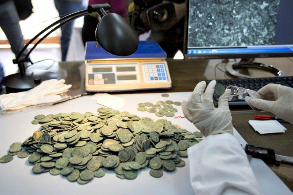 Portada - Los expertos del Museo Arqueológico de Sevilla, España, comienzan a catalogar las monedas del tesoro hallado recientemente en Tomares. (Fotografía: El País/Paco Puentes)