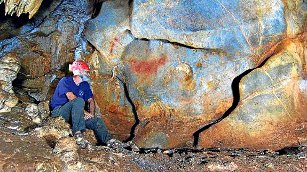Portada - Un espeleólogo del grupo ADES observa el caballo rojo, una pintura rupestre recientemente descubierta cuya datación definitiva aún no se ha realizado. (Fotografía: El Correo/ADES)