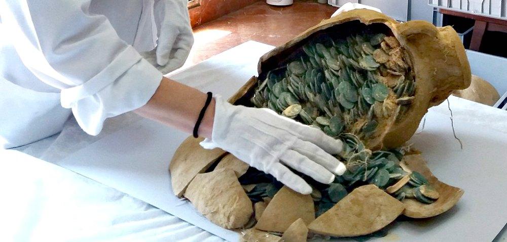 Portada-Una de las ánforas repleta de monedas es examinada en el Museo Arqueológico de Sevilla. (Fotografía: Paco Puentes/El País)
