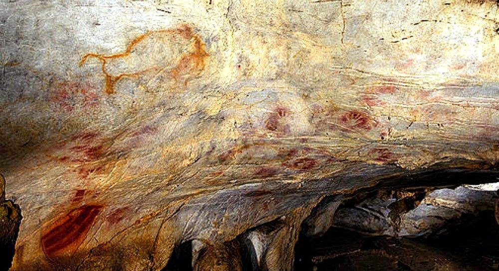 Portada - Fotografía del interior de la Cueva de El Castillo en Puente Viesgo, Cantabria (España), en la que pueden observarse algunas de sus pinturas rupestres prehistóricas. (Gabinete de Prensa del Gobierno de Cantabria/CC BY-SA 3.0)