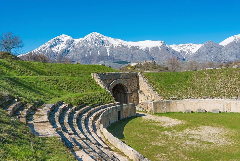 Alba Fucens, sitio arqueológico romano con anfiteatro. Monte Velino montaña con nieve, región de Abruzzo, Italia central Fuente: ValerioMei / Adobe Stock