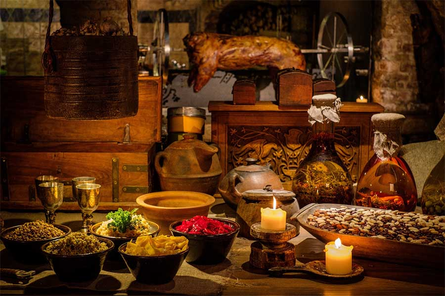 Mesa de cocina antigua medieval con comida típica en el castillo real. Nejron Photo / Adobe Stock