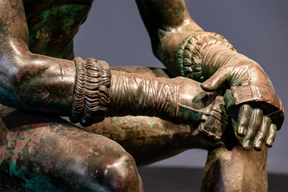 Detalle de The Boxer at Rest, escultura griega de bronce helenística de un Púgil desnudo sentado en reposo. Crédito: giorgio / Adobe Stock