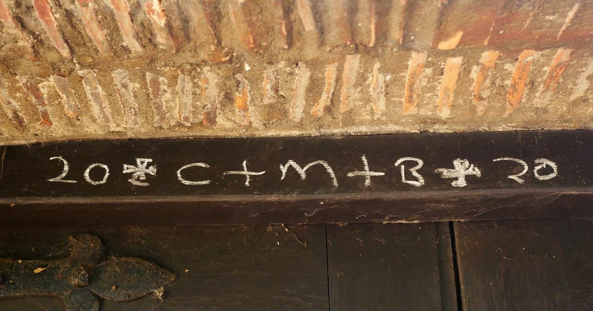 """Un ejemplo de tiza en la puerta que dice """"Cristo bendice esta casa"""" en la cara oeste de la Iglesia de San Miguel en Welling, Inglaterra, una tradición de la Epifanía."""