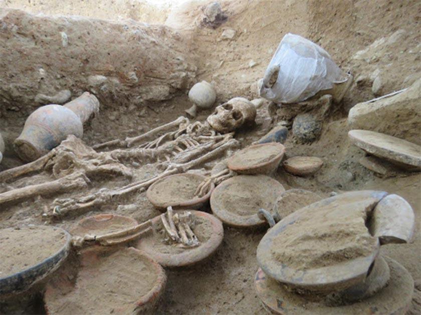 Vista de la cámara funeraria etrusca. En primer plano, cuencos y restos de animales y hacia atrás el difunto. Fuente: Roland Haurillon, Inrap