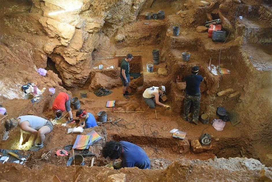 Fotografía que muestra el sitio de excavación en la cueva Lapa do Picareiro en el centro de Portugal. La excavación del humano moderno temprano se puede ver en primer plano y las capas de Neandertal en el fondo.