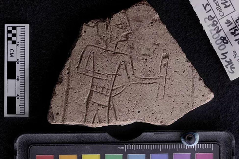 Un tacho grabado con una imagen de un escriba sosteniendo una paleta de tinta. Se encuentra cerca de una antigua mina de amatista egipcia.
