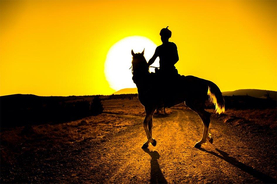 Representación de un guerrero parto montado en un caballo en la puesta de sol. Fuente: mehmetcan/ Adobe stock