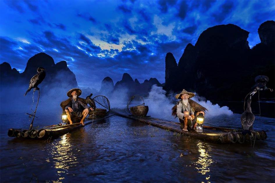 Pesca con cormoranes en el río Li durante la hora azul del amanecer, Guangxi, China.