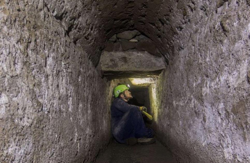 Túnel dentro del antiguo sistema de desagües de Pompeya con arqueólogo adentro. Fuente: Parque Arqueológico de Pompeya.