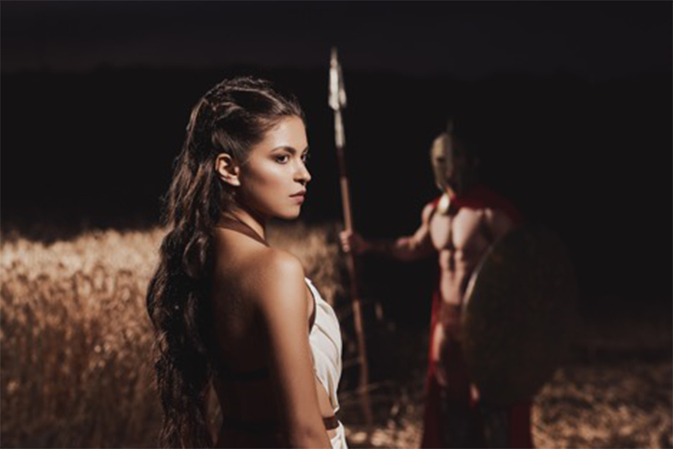 Mujer espartana en primer plano con su marido guerrero al fondo. Fuente: serhiibobyk/ Adobe stock
