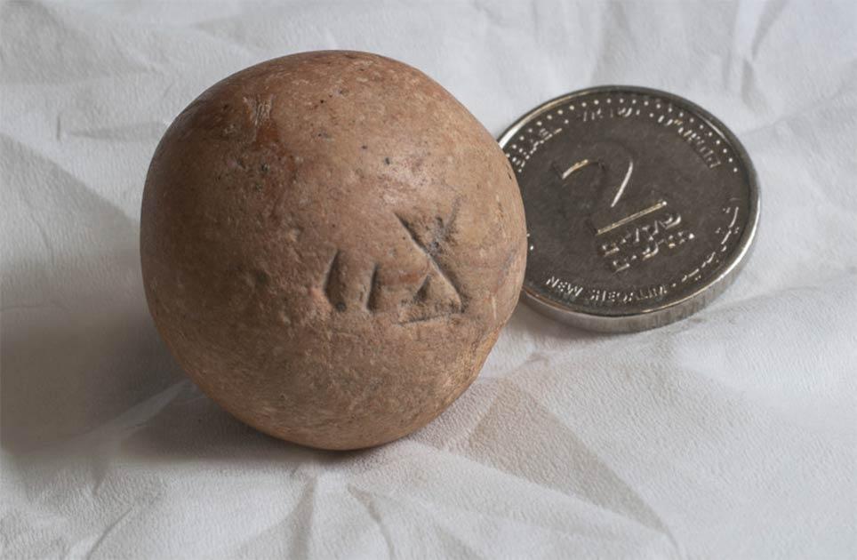 el antiguo peso de dos shekels, encontrado recientemente cerca del Muro Occidental en Jerusalén, junto a una moneda israelí moderna de dos shekels.