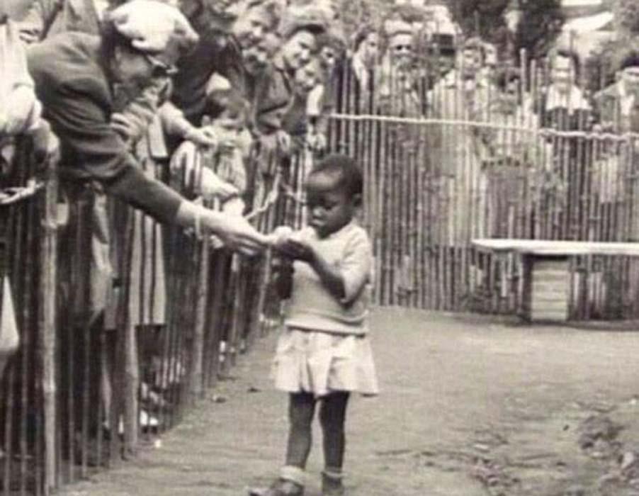 Se muestra a una niña africana en la Exposición de 1958 en Bruselas, Bélgica, que contó con un 'Pueblo del Congo' con visitantes que la observaban desde detrás de las cercas de madera