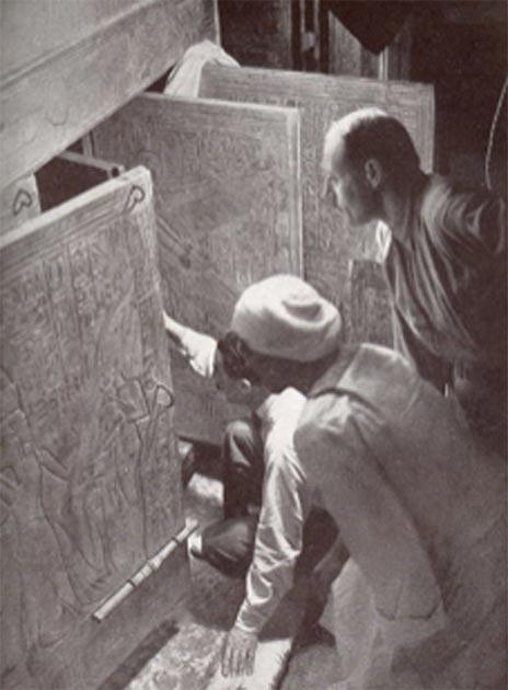 Howard Carter y sus asociados abriendo las puertas del santuario en la cámara funeraria de la tumba de Tutankamón. (Dominio publico)