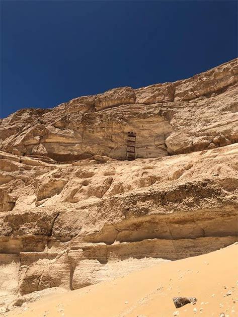"""Las aberturas descubiertas en lo alto de un acantilado son """"entradas a cámaras excavadas, que probablemente tienen una importancia religiosa sagrada"""". (Ministerio de Turismo y Antigüedades)"""