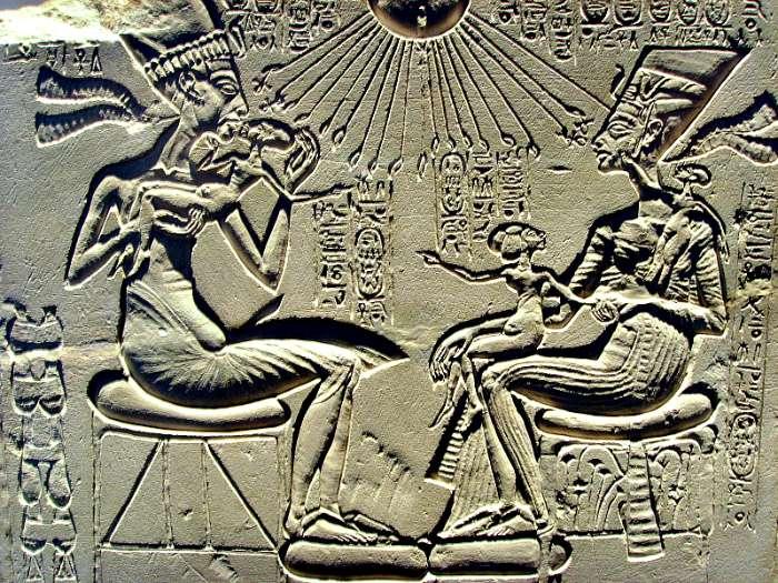 Relieve en caliza que probablemente formaba parte de un altar de adoración familiar. Akenatón sostiene en brazos a su primogénita Meritatón y, frente a ambos, Nefertiti sostiene en su regazo a Meketatón, su segunda hija -quien fallecería prematuramente- y en su hombro izquierdo a su tercera hija Anjesenpaatón, que se desposaría posteriormente con Tutankamón. Museo de Berlín. (Wikimedia Commons)