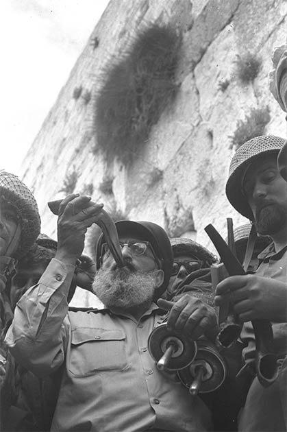 El 7 de junio de 1967, durante la Guerra de los Seis Días, el capellán jefe del ejército, el rabino Shlomo Goren, rodeado por soldados de las FDI, toca el cuerno del shofar frente al Muro Occidental en Jerusalén, declarando el regreso de los judíos al Monte del Templo después de dos milenios. -larga ausencia. (Oficina de Prensa del Gobierno (Israel) / CC BY SA 4.0)