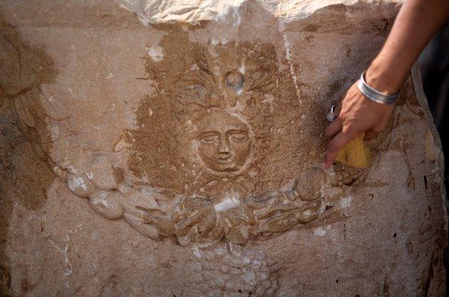 Un operario de la AAI limpia la Medusa esculpida sobre la superficie del sarcófago de piedra caliza. En la época romana se creía que Medusa era protectora de los muertos. (Huffington Post)