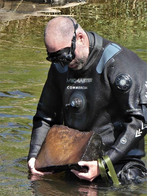 Bob Armstrong, del Equipo Marino y Costero de Arqueología de Wessex, mientras recupera una muestra de madera de un puente del río. El equipo de ADHS advierte que los restos del puente medieval están amenazados. (ADHS)