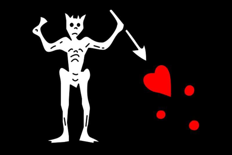 Bandera de Barbanegra compuesta por un esqueleto sobre fondo negro sujetando en la mano derecha un reloj de arena y en la izquierda una flecha apuntando a un corazón rojo goteando sangre. El reloj de arena significaba el correr del tiempo y que la muerte rondaba a sus enemigos. (Public Domain)