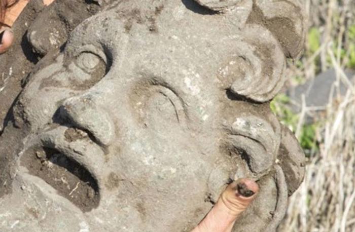 Un investigador de la Universidad de Haifa sostiene la singular máscara de bronce del dios Pan (Foto: Universidad de Haifa)