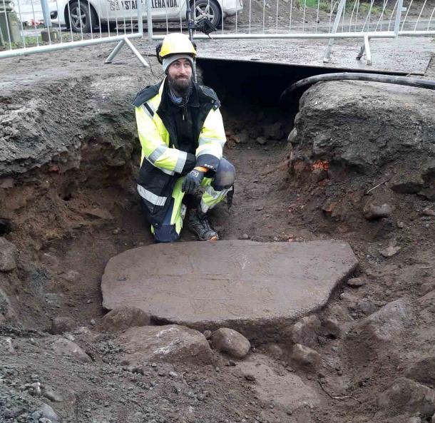 El arqueólogo Axel Krogh Hansen en la estatua que se encontró durante la excavación frente a una línea de alcantarillado. (Imagen: Annika Knarrstreöm / Arkeologerna)