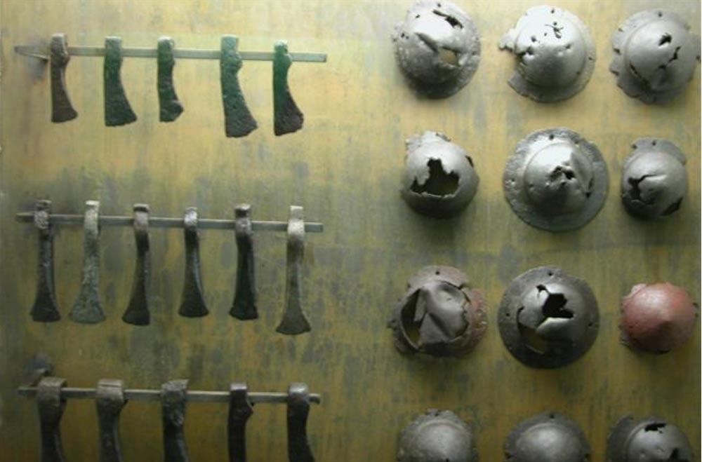 Objetos de hierro descubiertos en el pantano de Nydam, en Dinamarca. A la izquierda, hojas de hachas, a la derecha, piezas de escudos (umbos). (CC BY-SA 3.0)