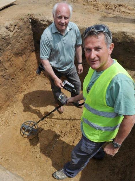 Los detectores de metales Reg Mead, izquierda, y Richard Miles, derecha, que encontraron el tesoro de monedas celtas en el sitio de excavación. (Jersey Heritage)