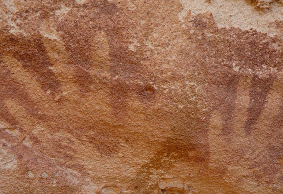 """Imágenes de las diminutas """"manos"""", cuyo modelo podrían haber sido las extremidades de algún reptil, en el interior de huellas de manos adultas pintadas sobre las paredes de roca de Wadi Sura II. (Emmanuelle Honoré)"""