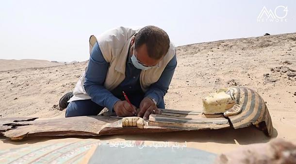 Otro de los antiguos sarcófagos egipcios desenterrados en el sitio arqueológico de Saqqara, siendo inspeccionado por un arqueólogo. (Ministerio de Turismo y Antigüedades de Egipto)