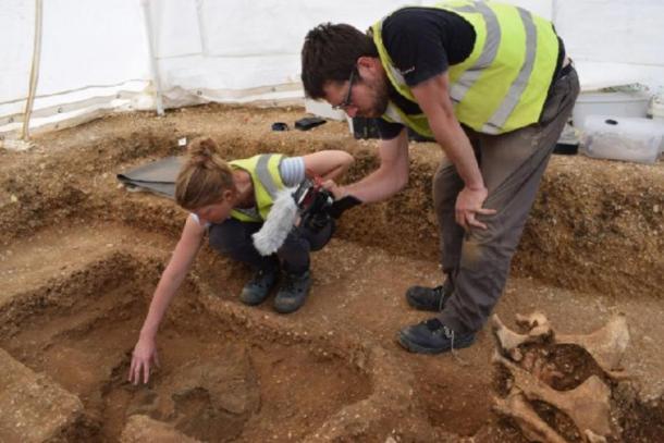 Arqueólogos desenterrando el escudo guerrero junto con los restos del hombre (MAP Archaeological Practice Limited)