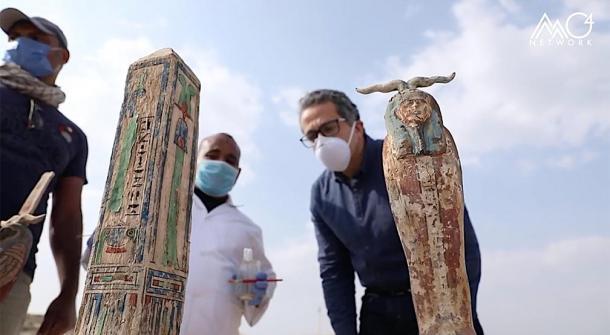 Los arqueólogos y Khaled El-Enany inspeccionan el antiguo obelisco egipcio y otra figura desenterrada en el sitio arqueológico de Saqqara. (Ministerio de Turismo y Antigüedades de Egipto)
