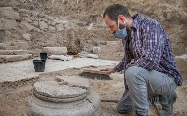 Un arqueólogo limpiando uno de los pilares sobre los que se construyó la iglesia bizantina de 1500 años. La iglesia fue encontrada en el área del jardín antes de que se descubrieran los baños rituales. (Yoli Schwarz / Autoridad de Antigüedades de Israel)