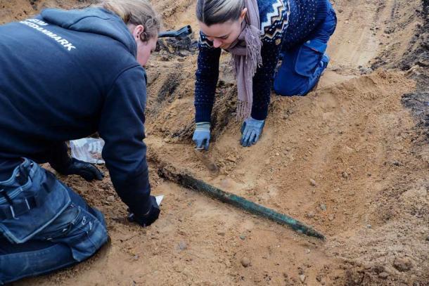 Arqueólogos extraen cuidadosamente la espada del sitio de excavación en Håre, Dinamarca (Museos de la ciudad de Odense)