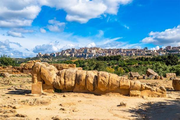 La estatua de Atlas acostada con la moderna ciudad italiana de Agrigento al fondo. (javarman / Adobe Stock)