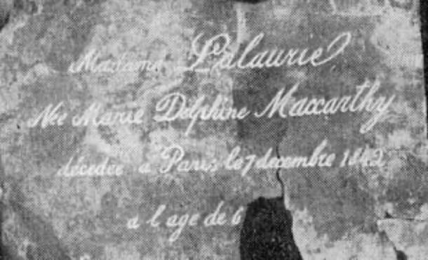 """Fotografía en blanco y negro de una placa de cobre encontrada en el cementerio St. Louis # 1 por Eugene Backes a fines de la década de 1930. El texto lee: """"Madame Lalaurie, nee Marie Delphine Maccarthy, falleció a Paris, le '7 decembre, 1842, a l'age de 6 -"""". (Uso justo)"""