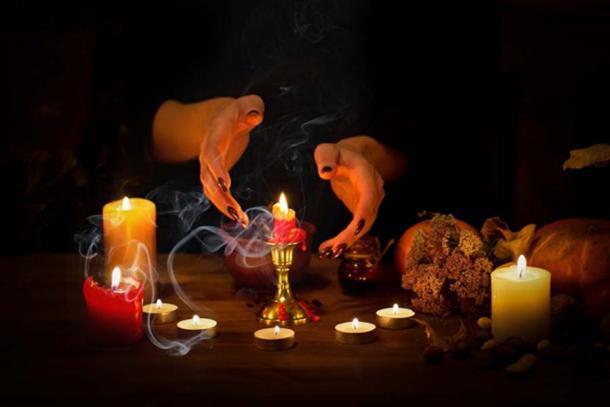 Representación de brujas haciendo pases sobre velas y cera en un altar en la oscuridad. (junky_jess / Adobe stock)
